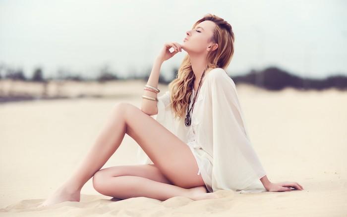 blond cendré, collier pendentif noir, femme sur la plage, chemise blanche avec manches en soi, cheveux longs légèrement bouclés
