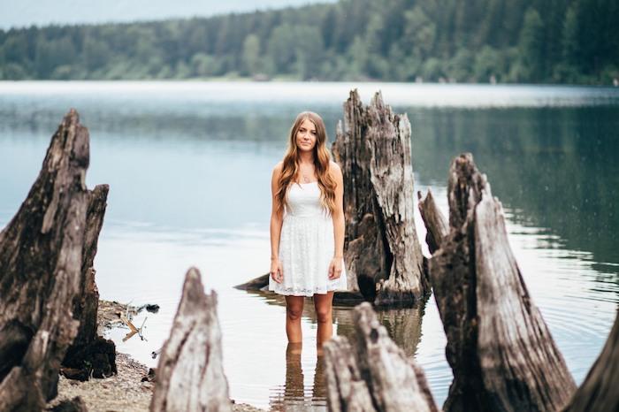 meche blonde, fille dans lac, robe blanche avec bustier et jupe en dentelle florale, cheveux balayage californien
