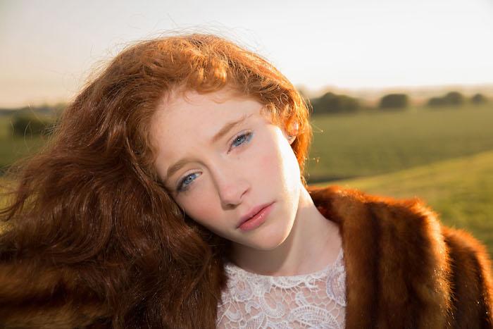roux cuivré, manteau en faux fur marron, robe blanche avec décolleté à motifs dentelle, yeux bleu et lèvres rose