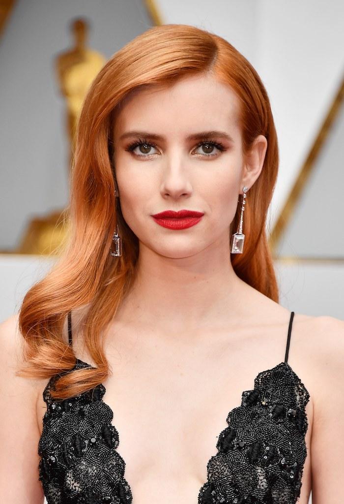 cheveux roux, célébrité, Emma Roberts, maquillage avec rouge à lèvre rouge et eye-liner noir, robe avec décolleté en noir