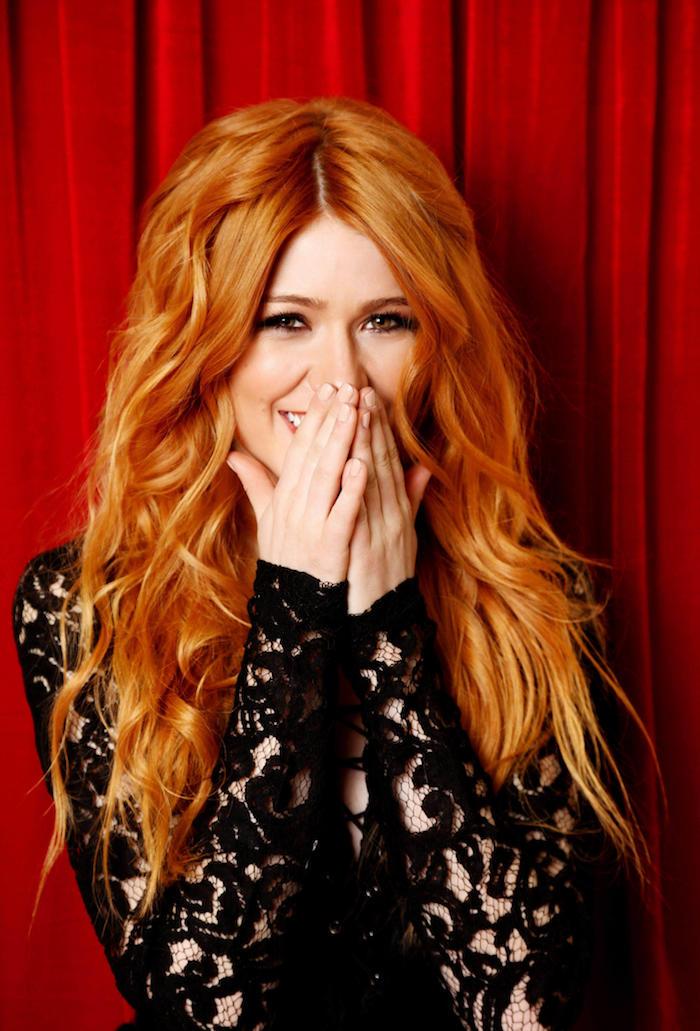 blond cuivré, coiffure avec boucles, robe noire avec manches longues en crochet, photo de fond rouge