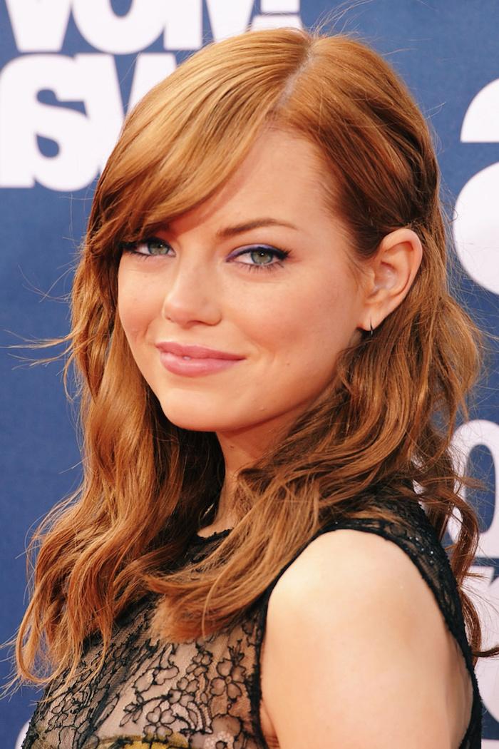 couleur de cheveux rouge, Emma Stone, coiffure sur le côté avec frange, coupe de cheveux femme, yeux verts