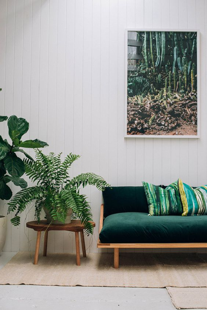 salon blanc qui adopte la décoration nature et les nuances de vert canard et de vert émeraude, canapé en velours vert émeraude avec des coussins imprimés
