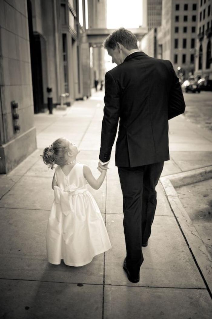 une adorable photo mariage en noir et blanc d'une petite fille d'honneur accompagné de marié