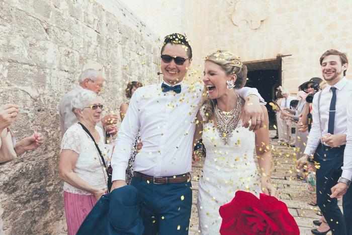 photo de couple heureux sous une pluie de confettis, photo mariage à la sortie de l église