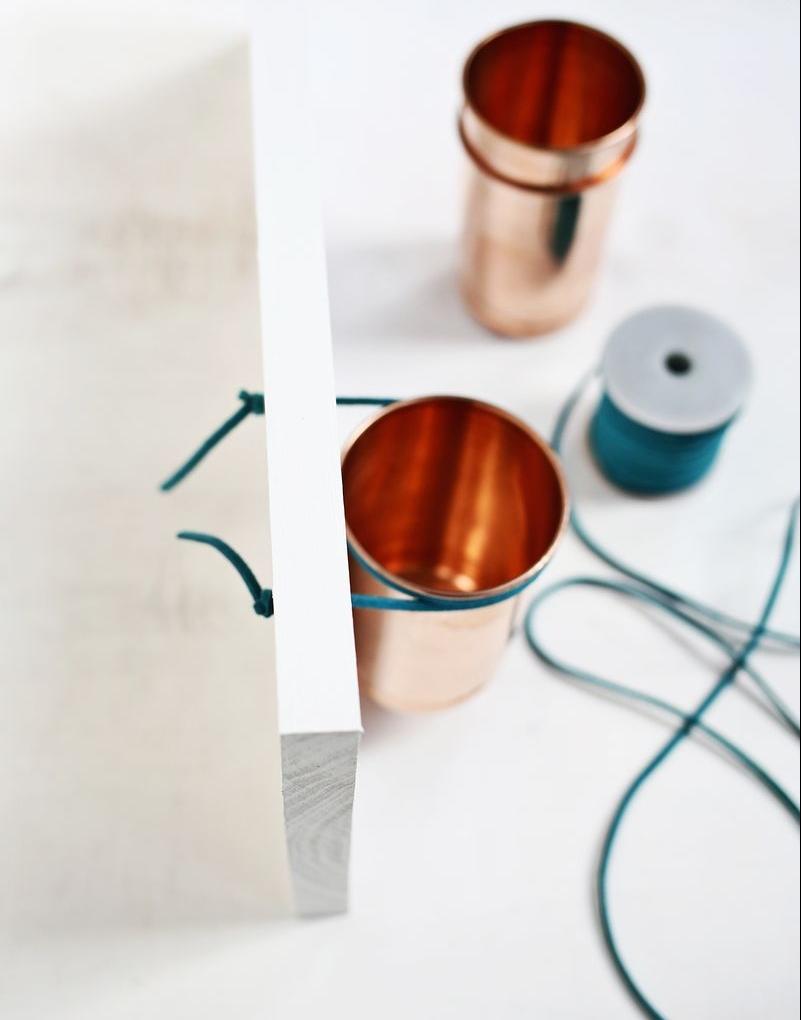 fixer les pots en cuivre à la planche de bois, repeinte en blanc, avec un cordon bleu, idée pour fabriquer un rangement maquillage soi meme