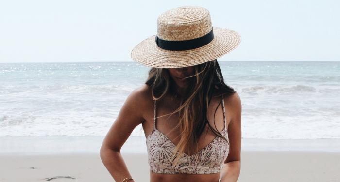 blond foncé, cheveux longs aux racines marron et mèches blond doré, capeline beige et noir, maillots de bain avec bretelles motifs tropicales