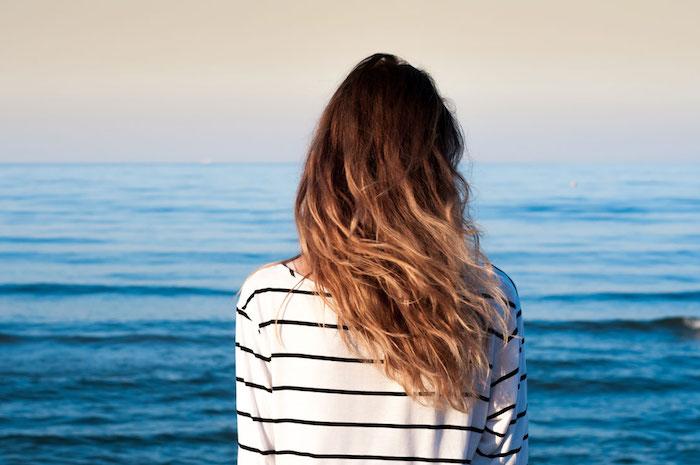 cheveux blond foncé, fille au bord de la mer, cheveux longs en boucles, coiffure cheveux détachés en blond châtain