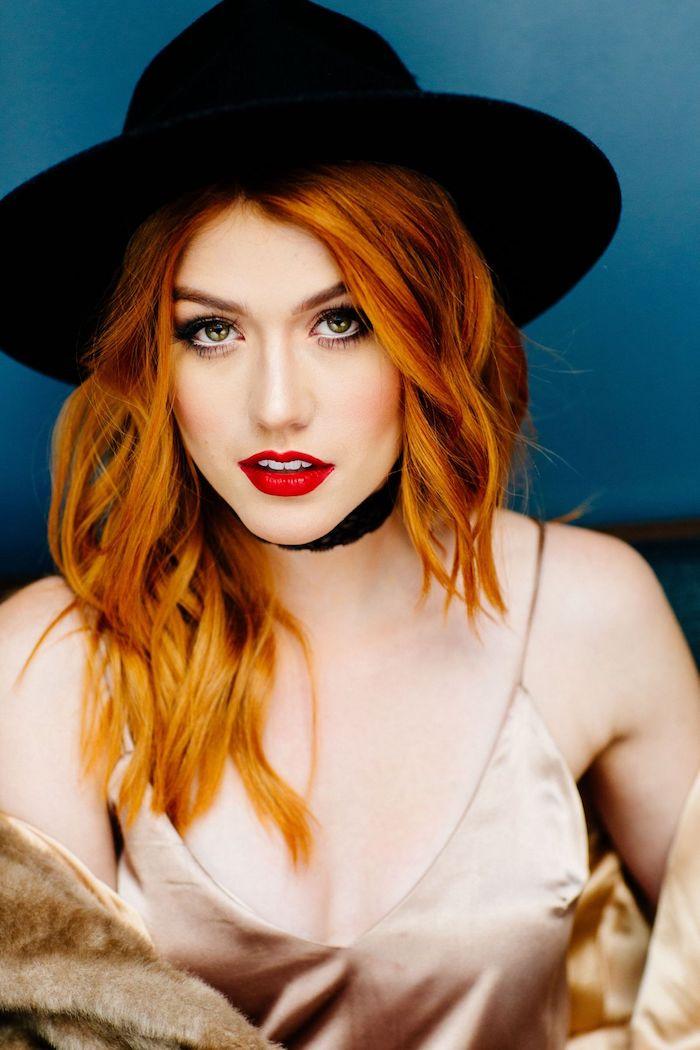 cheveux roux, rouge à lèvre nuance rouge, coupe de cheveux mi longs en nuance orange, capeline noire, manteau en faux fur beige