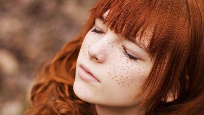 coloration roux, fille avec tâches de rousseur sur le visage, coiffure avec boucles et frange