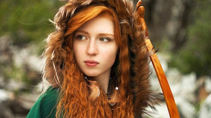 blond roux, femme dans la nature, look sauvage avec plumes dans les cheveux, manteau vert avec capeline en fourrure