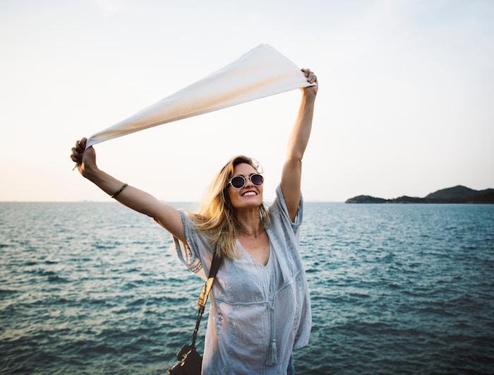 blond cendré, appareil photo sur l'épaule, chemise en bleu clair avec pendentif pompon, lunettes de soleil rondes