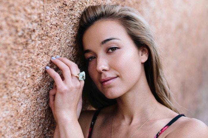 blond foncé cendré, ongles courts à vernis bleu, bague en or avec pierre turquoise, yeux marron et lèvres rose