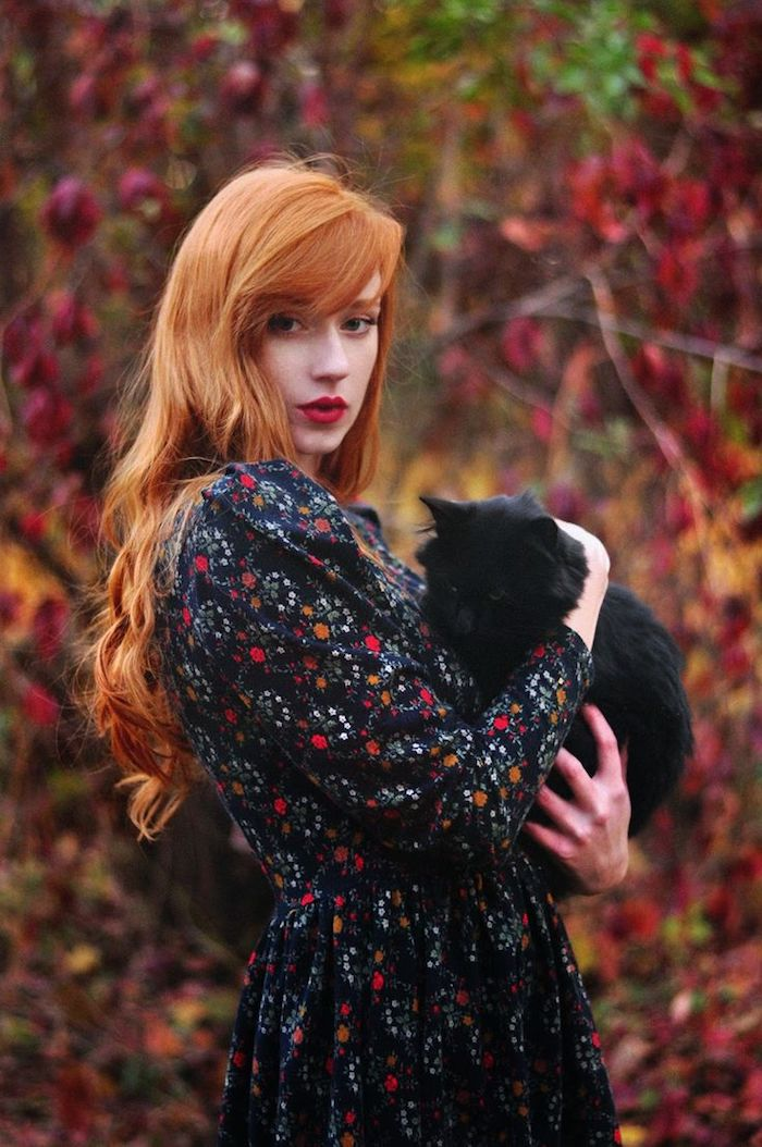 roux cuivré, femme dans la forêt, animal de compagnie chat noir, coiffure orange avec boucles, rouge à lèvres nuance rouge