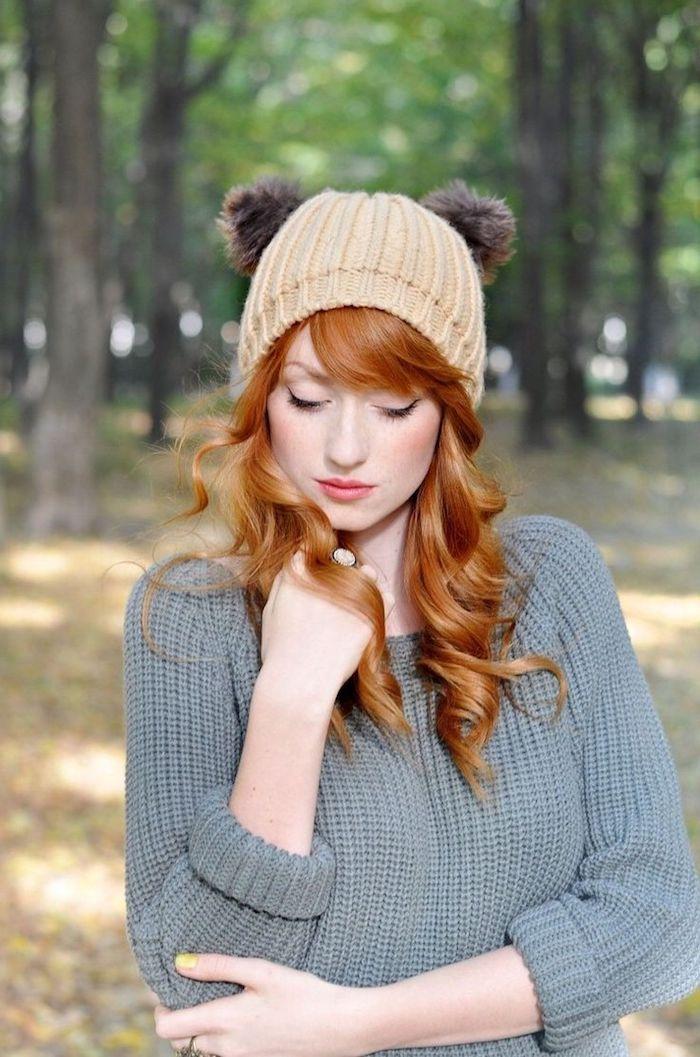 coloration roux, bonnet en beige, vernis à ongles jaune, pull en crochet gris, femme dans la forêt, cheveux orange