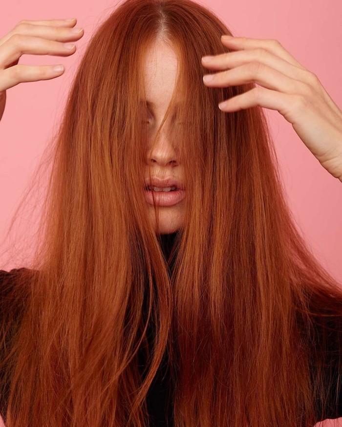 couleur rousse, cheveux longs et raids, femme au maquillage naturel avec lèvres rose, photo avec fond rose