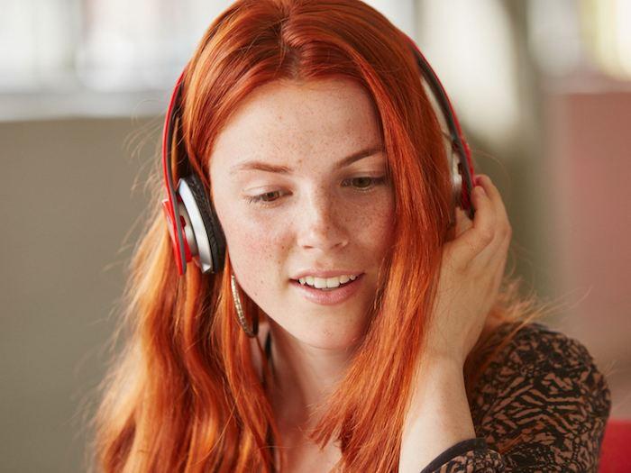 roux auburn, coupe de cheveux mi longs, écouteur modèle femme en rouge et noir, rouge à lèvres rose