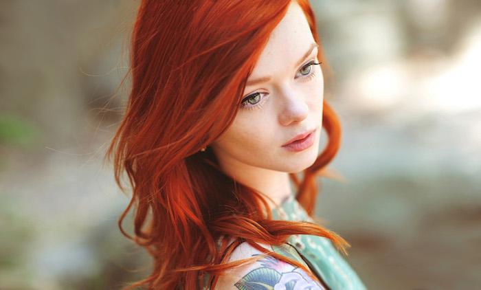coloration roux, tatouage sur l'épaule en couleurs, maquillage avec eye-liner noir, coupe de cheveux mi longs bouclés