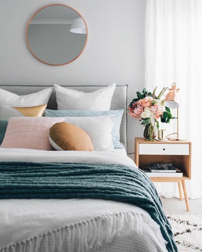 gris perle chambre a coucher avec miroir rond au dessus du lit avec des coussins bleuatres