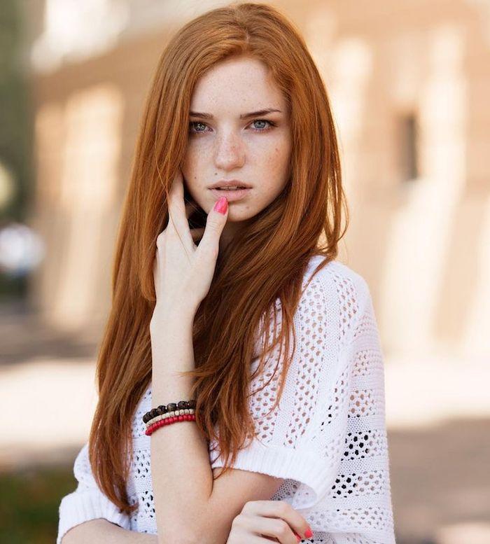roux cuivré, bijoux en perles de bois, vernis à ongle rouge, yeux verts, cheveux longs en nuance orange