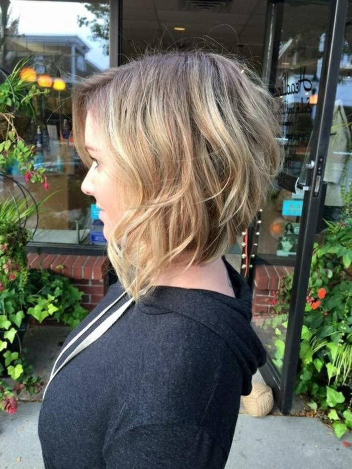 carré plongeant court coupe de cheveux femme blond et mèches chatains frangé sur le coté