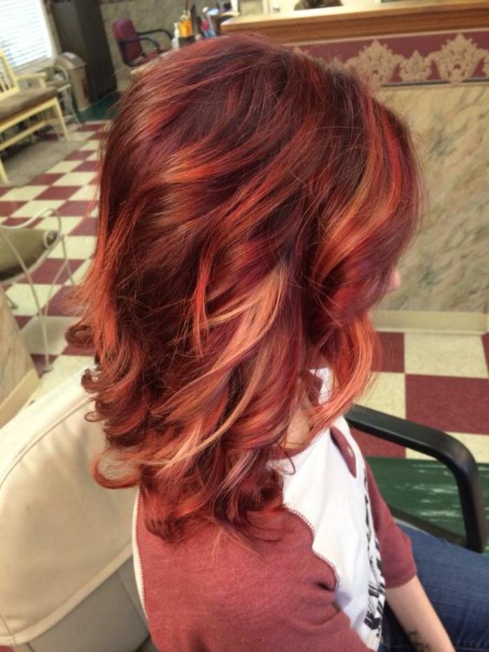 coupe asymétrique en couleur bourgoundiavec des mèches colorées en diverses nuances du rouge