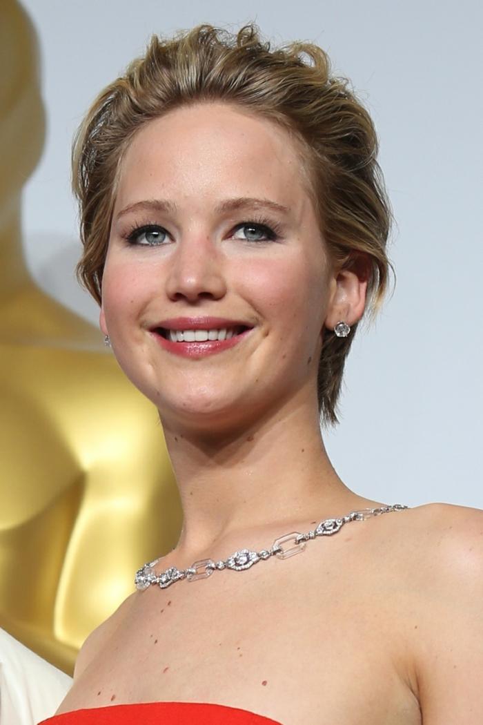 coupe courte blonde, collier chaîne argenté, maquillage élégant pour yeux bleus