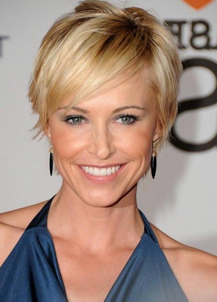 coupe de cheveux courte femme, coiffure effilée blonde, maquillage discret et robe bleue