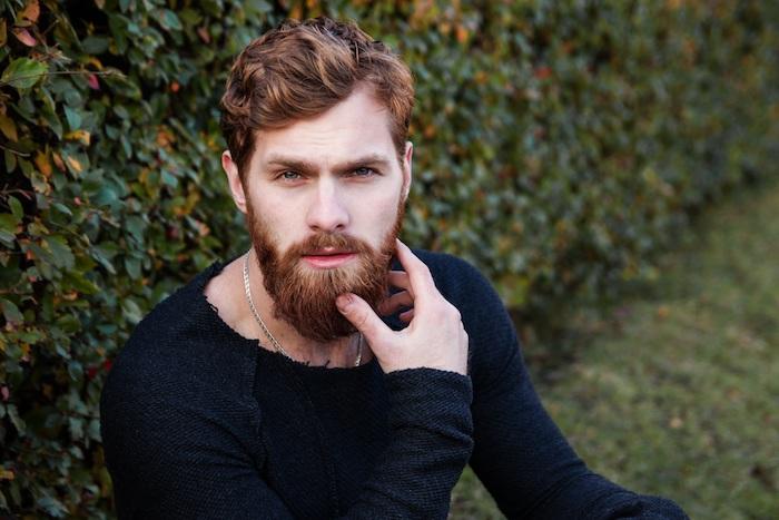 homme brun, blouse noire aux manches longues, collier en argent homme, cheveux ondulés et barbe longue en cuivre