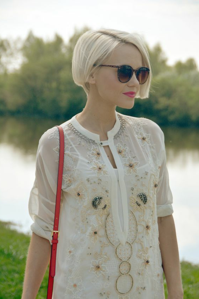coupe femme court, chemise blanche et lunettes de soleil, sac rouge portée épaule