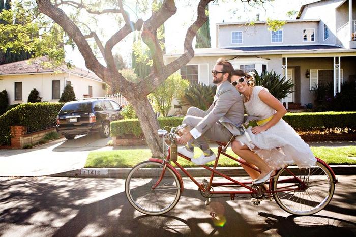 cliché de couple original, photo mariage décontractée et toute naturelle des mariés sur vélo