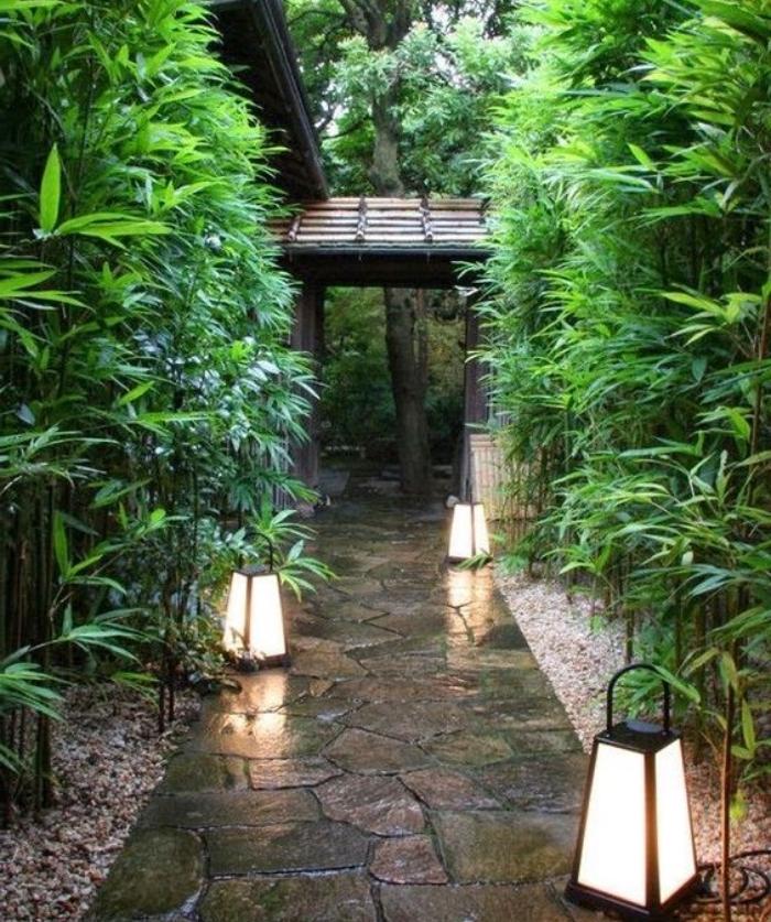 une chemin entrée cour maison, sentier de pierres avec bambou des deux côtés et lanternes comme éclairage exterieur