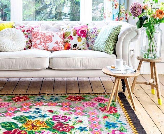 idée de shabby chic boheme style dans un salon, canapé blanc, tapis et coussins fleuris, rideaux bleus à fleurs, tabourets en bois, grandes fenêtres