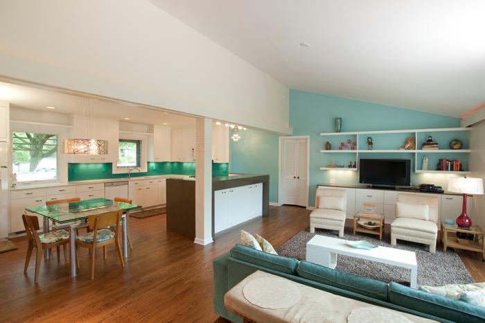 amenagement petite cuisine façade blanche, crédence verte, parquet marron, salle à manger avec table en verre et chaises en bois, canapé vert d eau, table basse blanche, tapis gris, fauteuils blancs, meuble tv blanc, mur d accent bleu