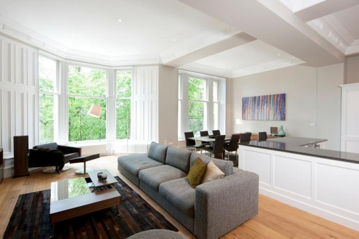 aménager petit salon salle à manger, petite cuisine équipée avec ilot central blanc et plateau en bois marron foncé, salon avec canapé gris, tapis marron et table basse en bois, parquet clair