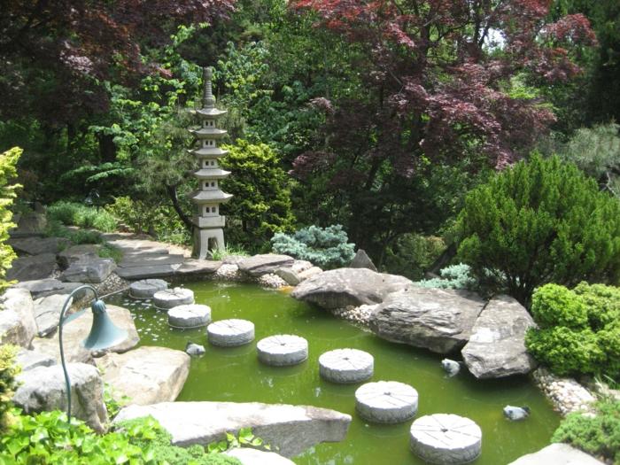 idée amengament jardin zen japonais, un chemin de pierres dans un bassin d eau, statuette temple japonais, arbres et arbustes