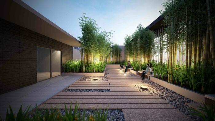 maison moderne avec une cour exterieure énorme, revêtement de galets avec des dalles en bois au dessus, coin détente, entouré de bambou