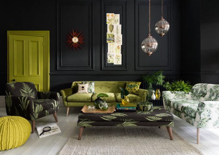 tissu tropical, comment décorer le salon, murs peints en noir, horloge soleil rouge, canapé en velours vert, tapis beige, plantes vertes