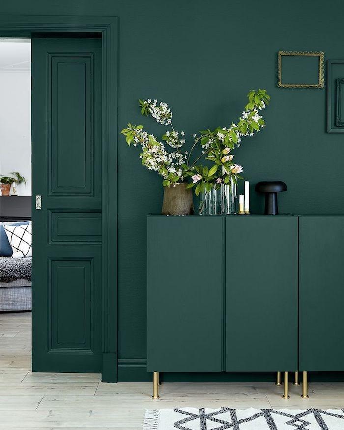 tapis motifs géométriques, murs peints en vert foncé, meubles en bois avec pieds en cuivre, revêtement de sol en bois claire