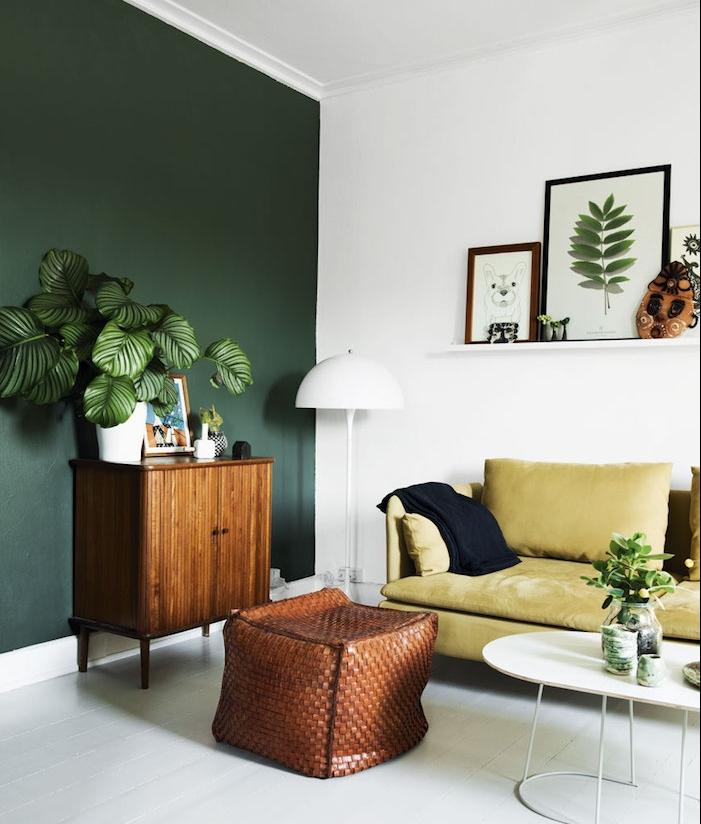 oasis tropical, salon aux murs vert et blanc, cadres photos en bois, lampe sur pied en blanc, canapé en velours jaune