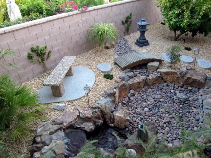 decoration zen jardin, une chute d eau, entourée de grosses pierres, avec une bassin de galets et gravier pour le reste, un petit pont en bois et banc en pierre pour se détendre, lanterne