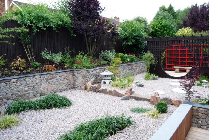 jardin zen japonais, un bassin recouvert de gravier, petits arbustes verts, lanterne en pierre, plus grosses pierres, cloture en bois