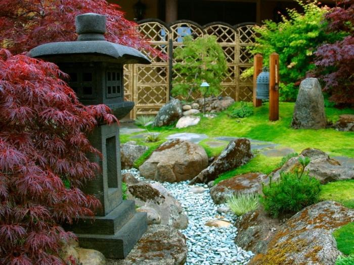 idée comment aménager un jardin zen minimaliste, gazon, rivière en pierres, entouré de grosses pierres, lanterne, lampe en pierre, arbres et plantes japonaises