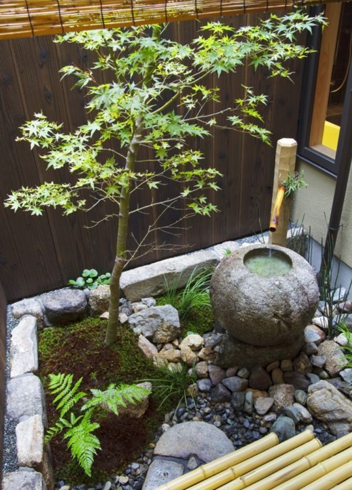 fontaine d eau dans un carré zen du jardin, decoration zen de galets, pierres, bambou et arbre, cloture en bois et bambou