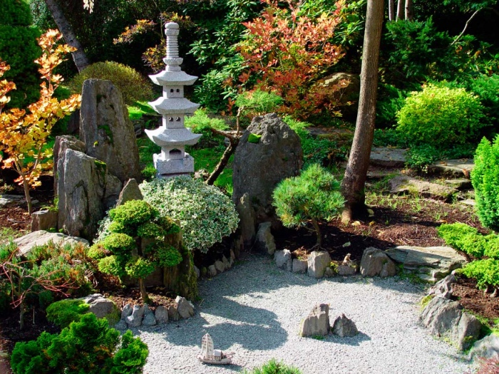 jardin zen minimaliste, gravier, pierres sur le sol, arbustes et petits arbres, petit temple en pierre, vegetation verte