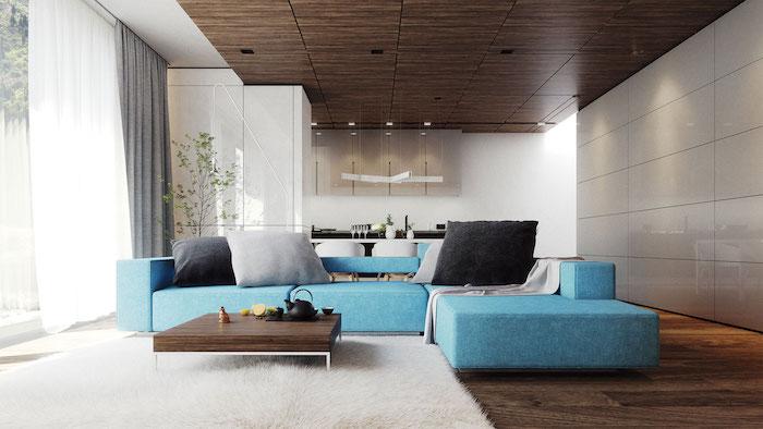 canapé velours, revêtement de sol et de plafond en bois marron, rideaux longs en gris et blanc, murs blancs, canape d'angle en bleu claire