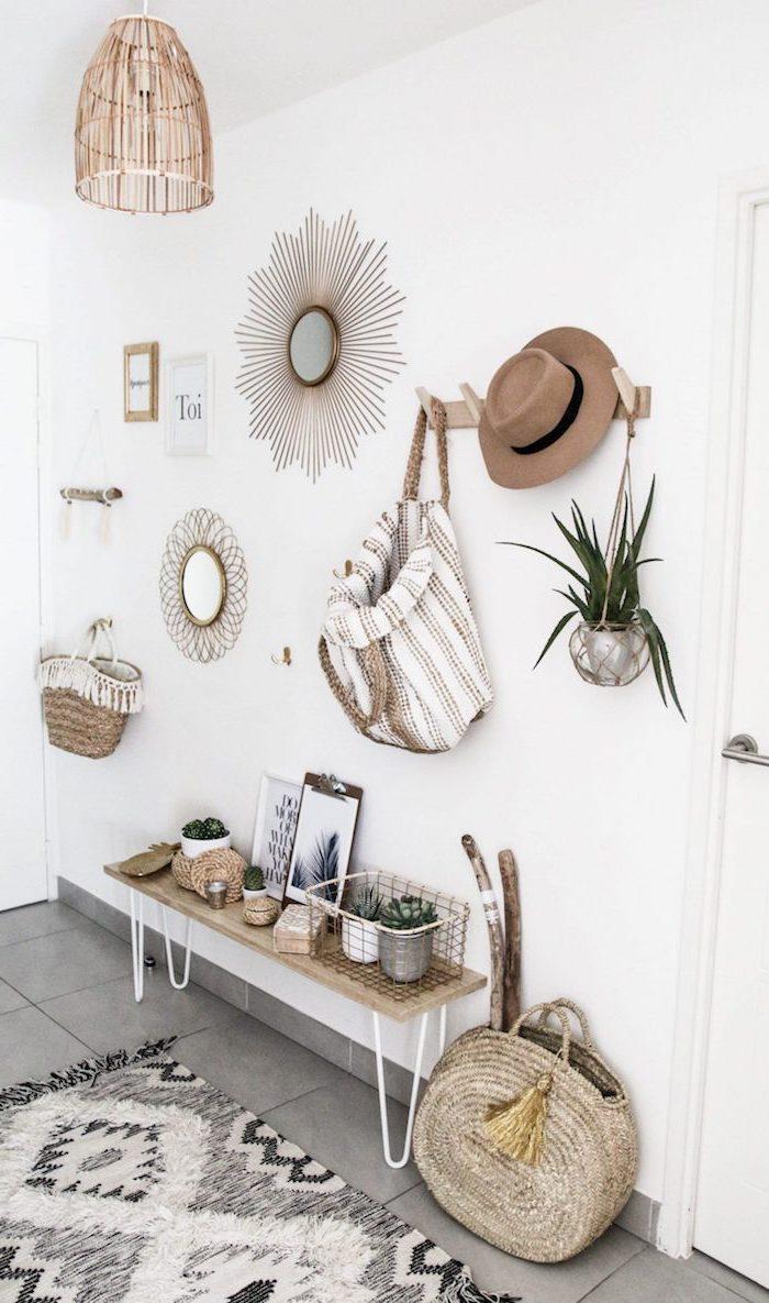 meuble scandinave, carrelage de sol en gris, objets en fibres végétales et bois, chapeau beige avec ruban noir, sac à dos blanc et beige, lampe suspendue en bois