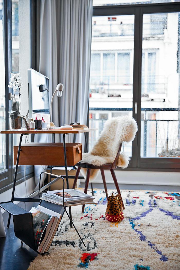 décoration appartement, bureau en bois, étagère magazine, rideaux longs et gris, tapis blanc en faux fur, chaise en bois avec housse blanche
