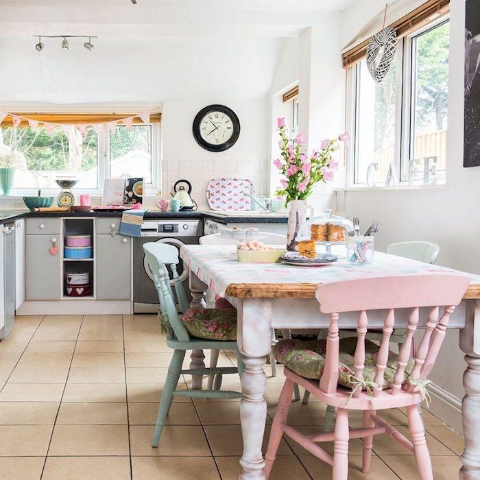 façade cuisine, table en bois et marbre, carreaux beige, mur couleur blanche, chaises en bois bleu et rose pastel, horloge vintage