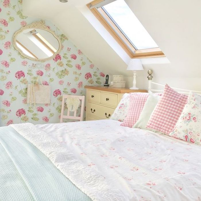 chambre shabby chic decoration féminine, linge de lit blanc, motif petites fleurs, coussins carré et fleuris, papier peint bleu fleurs rosse, commode beige vintage, deco chambre sous pente